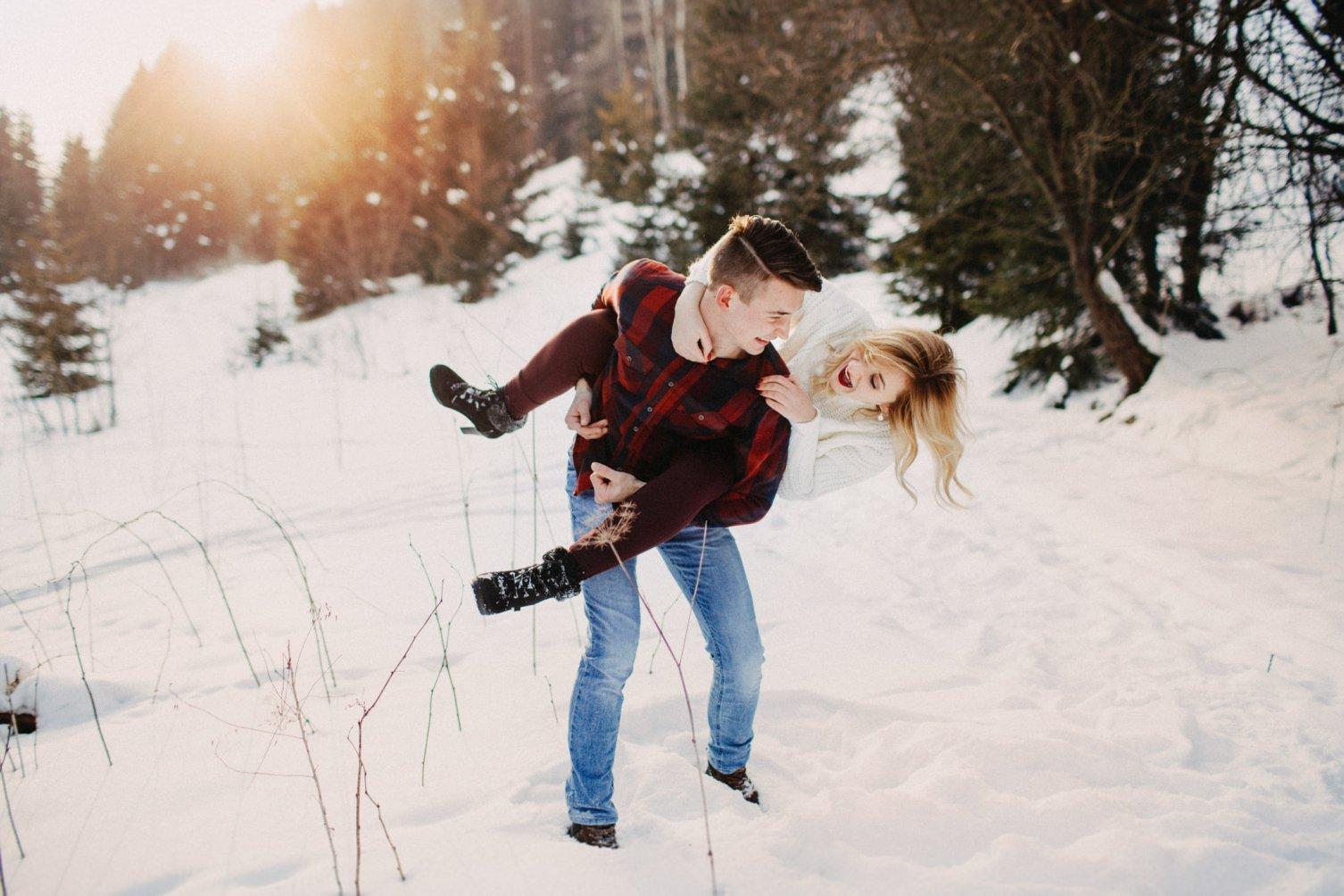 zimné rande fotenie. Spontánny párik na snehu pri západe slnka pod dekou.
